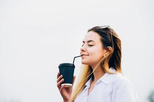 vacker tjej som dricker kaffe, ler, stängda ögon, kopieringsutrymme foto