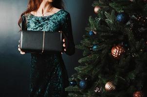 vacker kvinna med presentförpackning nära julgranen foto