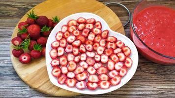 jordgubbsskivor på en vit tallrik i form av ett hjärta foto
