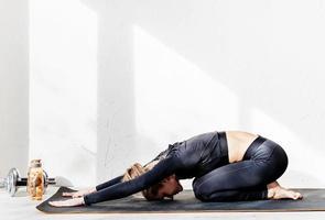 ung atletisk kvinna som tränar eller gör yoga som sträcker sig hemma foto