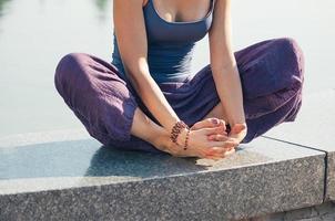 kvinna i lotus yogaposition utomhus, kroppsdel foto