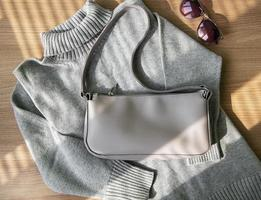 liten beige läderväska och grå damtröja foto