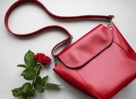rött läder kvinnor väska och ros på grå bakgrund foto
