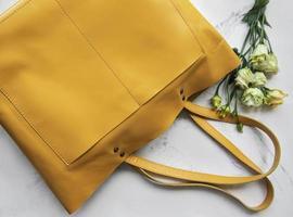 stor gul läderväska och blommor på marmorbakgrund foto