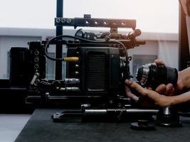 mänsklig hand som sätter in bioobjektivet i ett filmkamerafäste. foto