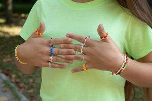 ringar och armband - pärldekorationer på flickans händer foto