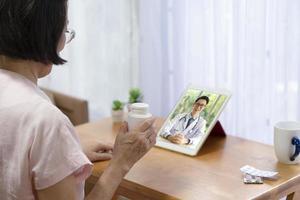 senior kvinna konsultera läkare online via videosamtal foto