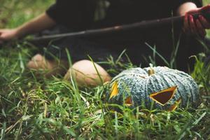 grön pumpa lykta på gräs med kvinnlig trollkarl som håller trollspö foto