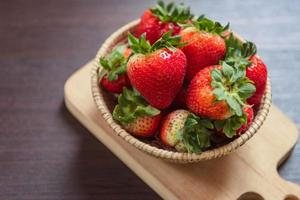 jordgubbe i korg på träbord. frukt och grönsaker foto