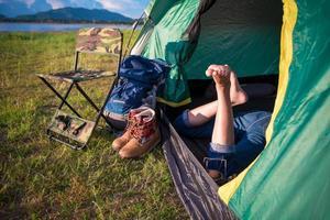 närbild av kvinnaben som kopplar av i campingtältet foto