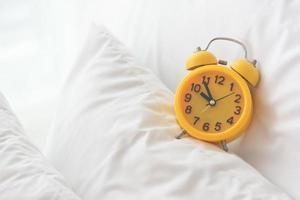 gul väckarklocka på vit säng bakgrund foto