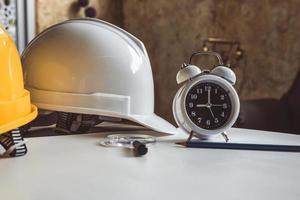 närbild av klocka och teknisk skyddshjälm på ritning bord foto
