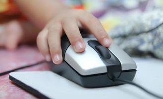 barnet lär sig online och spelar spel på datorn hemma. foto