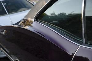 bakrutan och kurviga dörrdetaljer av en lila klassisk amerikansk bil foto