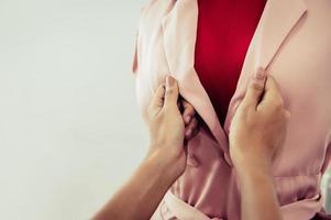 närbild skräddare hand knapp upp rosa pastellfärg foto