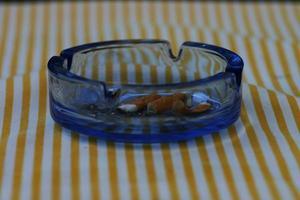 gulrandig bordsduk, askkopp och rumpor. foto