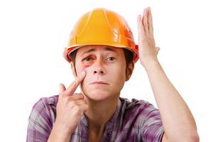 kvinnlig arbetare med ett svart öga i hjälmen foto