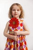 liten flicka med en röd blomma foto
