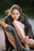 vacker ung kvinna som sitter på en bänk foto