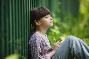 glad liten flicka som sitter och drömmer foto