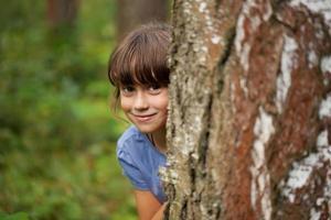 liten flicka som kikar ut bakom en trädstam foto