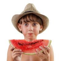 söt tjej i hatt äter mogen vattenmelon foto