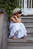 ledsen liten flicka som sitter ensam foto