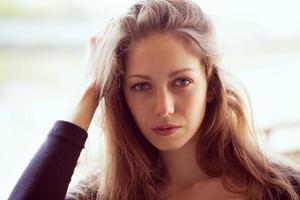 vacker kvinna rätar ut långt mörkt hår foto