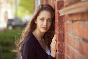 vacker kvinna nära en tegelvägg foto