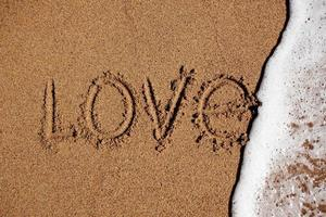 ordet kärlek på stranden tvättas av med vatten foto