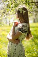 vacker flicka som står i trädgården foto