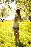 gullig flicka som står i trädgården foto