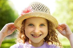 glad leende liten flicka i en hatt foto