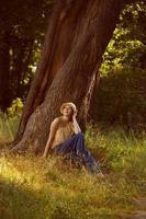 romantisk ung kvinna som sitter under ett träd foto