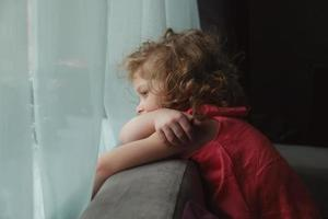 tjej som väntar på någon och tittar ut genom fönstret foto