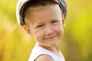 glad leende liten pojke i en keps foto