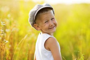 glad leende pojke i en grå keps foto