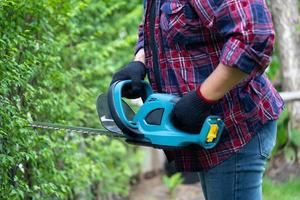 trädgårdsmästare som håller en elektrisk häcksax för att klippa trädtoppen foto