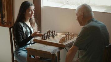 flickan förklarar hur man spelar schack mot mannen som sitter vid bordet foto