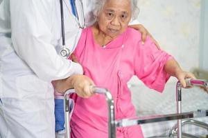 asiatisk läkare vård, hjälp och stöd senior patient promenad med rollator foto