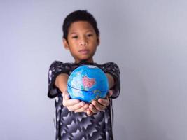 pojke som håller en jordglob sticker ut framför. foto