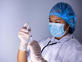 studioporträtt av en kvinnlig läkare med mask och hatt. foto