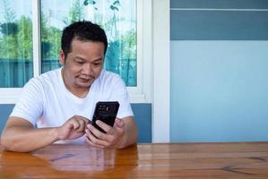 asiatisk man som bär vit skjorta med telefonen på ett träbord foto