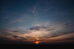 vacker solnedgång över ett mörkt landskap. dramatisk solnedgång foto