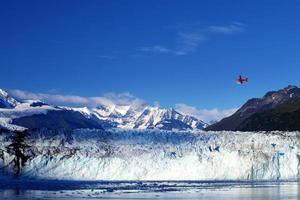 ett litet rött plan flyger över ett isberg foto
