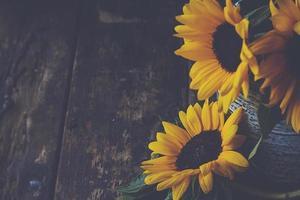 närbild av gula blommor på ett gammalt vintage träbord foto