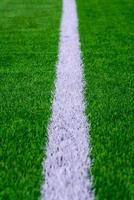 vit linje på grönt gräs på en fotbollsplan. selektivt fokus foto
