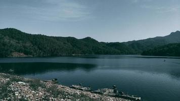 sjö- och bergsbakgrund i thailand. mörk ton foto