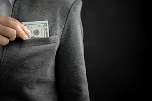 affärsman som döljer pengarräkning i fickan med kopiautrymme foto