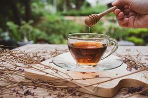 närbild hand tillsätt honung i galss av varmt te foto